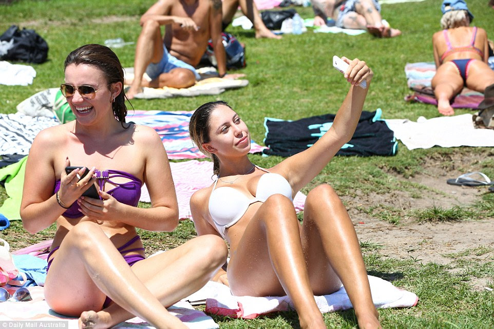 Sasha Boljevic (R) from Parramatta takes a selfie while sunbaking with her friend Maria Lukasheva from Silvania (L) on the grassy knowl at North Bondi