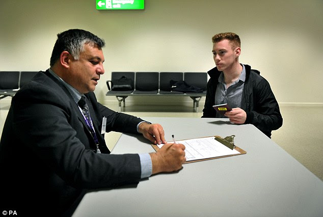 This photograph issued by Public Health England shows a passenger completing an interview at Heathrow