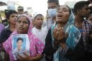 Relatives mourn as they show a picture of a garment worker, who is believed to be trapped under the rubble of the collapsed Rana Plaza building, in Savar