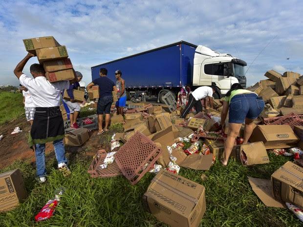Pessoas saqueiam carga de um caminhão que transportava alimentos e tombou na lateral da Via Dutra, na altura do km 124, sentido São Paulo-Rio de Janeiro, em Caçapava (SP). Ninguém se feriu no acidente (Foto: Lucas Lacaz Ruiz/Estadão Conteúdo)