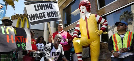 Part-time McDonald's maintenance worker Robert Wideman, 55, shines the shoe of Ronald McDonald during a protest outside a Hollywood McDonald's. (photo: Liz O. Baylen/LA Times)