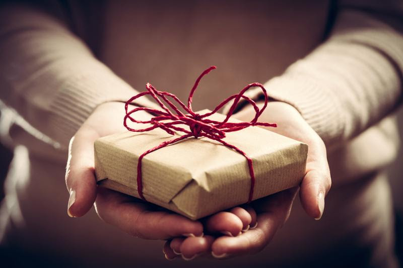 Giving a gift_ handmade present wrapped in paper. Christmas time_ vintage mood.