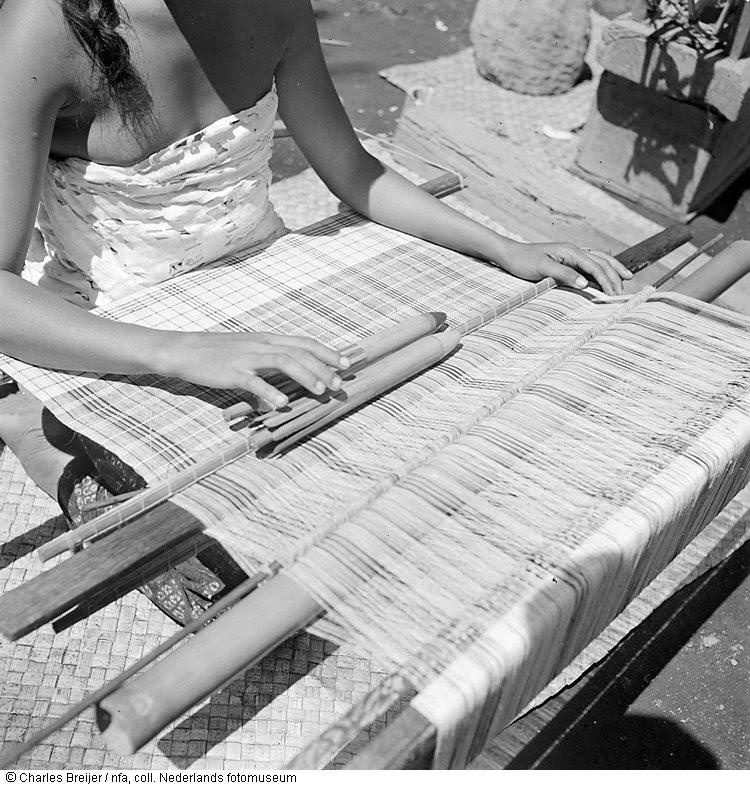 Detailopname van een meisje, werkend aan een weefgetouw in een kampong op Bali vanwege een filmopname, gemaakt door Jaap Zindler, Indonesië (1947)