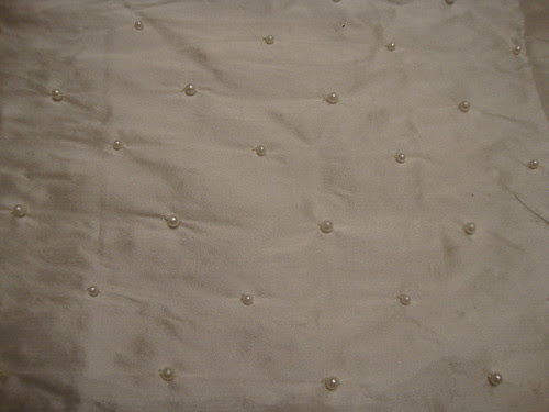 Closeup of ivory silk fabric with white beading
