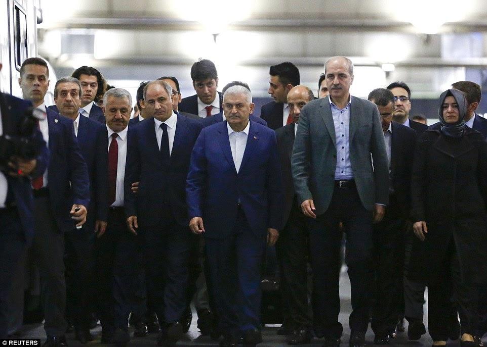 O primeiro-ministro da Turquia Binali Yildirim (centro) sai depois de uma conferência de imprensa no aeroporto Ataturk, em que ele disse que todas as indicações iniciais apontam para ISIS como sendo o responsável pelo ataque