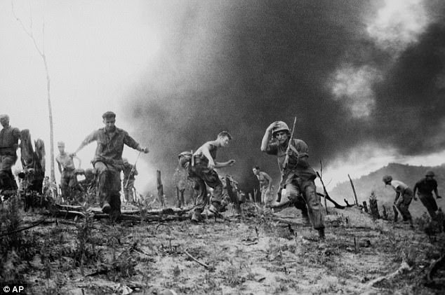 The Americans were caught largely unawares, because logic suggested that the Tet offensive was military madness. Pictured: U.S. Marines scatter after a helicopter is shot down in Vietnam
