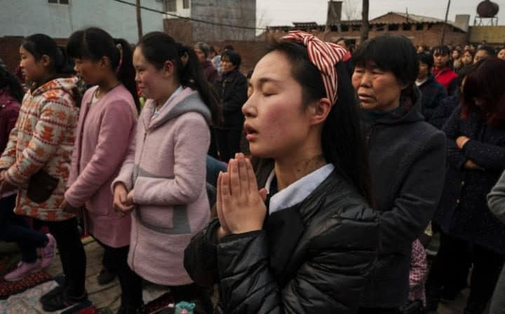 Villagers pray at the service