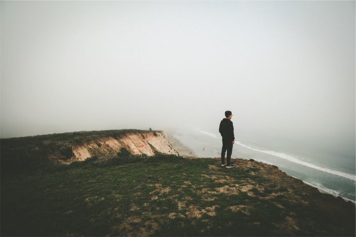 A man looking over a cliff toward the ocean.