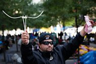 Michael Pellagatti, of Jersey City, N.J., holds the plastic  handcuffs police used to arrest him for disorderly conduct while  marching on the Brooklyn bridge along with the resultant court summons,  Sunday, Oct. 2, 2011, in New York. Over 700 protestors from the Occupy  Wall Street protests camping in nearby Zucotti park were arrested when  they marched on the Brooklyn bound lanes while protesting against  corporate greed. (AP Photo/John Minchillo)