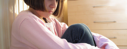 young girl sitting down with kness curled up looking depressed