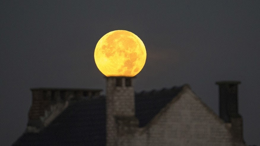 """File photo - A supermoon appears behind a house after a total """"supermoon"""" lunar eclipse in Brussels Sept. 28, 2015. (REUTERS/Yves Herman)"""