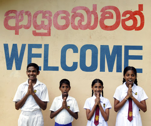 "Four children saying ""Ayubowan"" in front of a wall painted with ""Welcome"" in blue and ""Ayubowan"" in red and Sinhala."