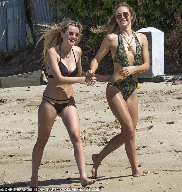 Sunkissed sisters: Strolling alongside the azure waters with her younger sister, Suki - who famously dated Bradley Cooper for two years till splitting in March - flaunted her incredible beach body