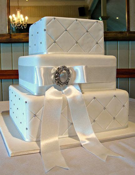 Three tier rectangular quilted white wedding cake with