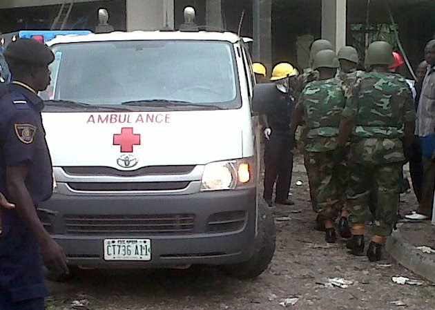 This image released by Saharareporters shows an ambulance, firefighters and rescue workers after a large explosion struck the United Nations' main office in Nigeria's capital Abuja Friday Aug. 26, 201
