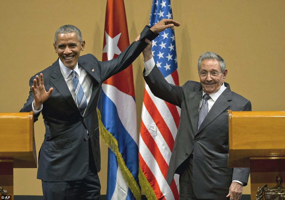 GRIN AND BEAR IT: Obama slapped on a smile as Castro grabbed his arm and put it up the air in a show of unity between the nations