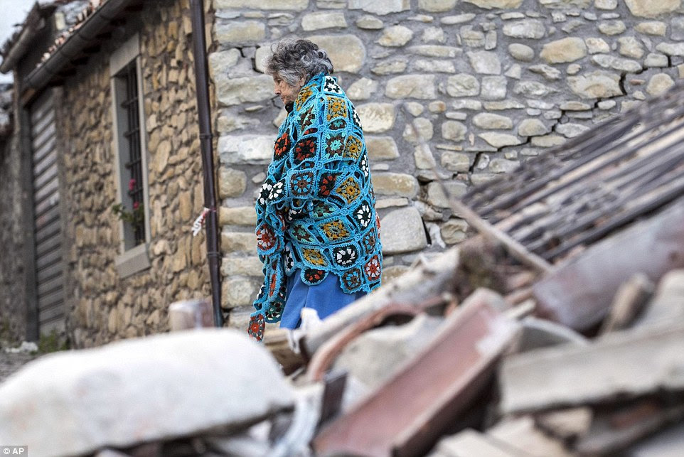 A woman walks past rubble following an earthquake in Amatrice. Hundreds of volunteer rescuers have joined the hunt for survivors
