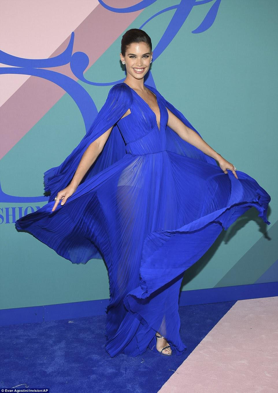 Que entrada!  O modelo Sara Sampaio exibiu sua forma de ajuste em um vestido azul elétrico plissado;  O vestido semi-sheer tinha um baixo decote, uma cintura cincada e um elemento caped