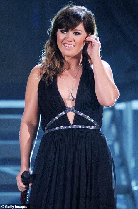 Rocha para fora!  Cantora Kelly Clarkson realizada e olhou slinky em um baixo vestido estilo grego corte