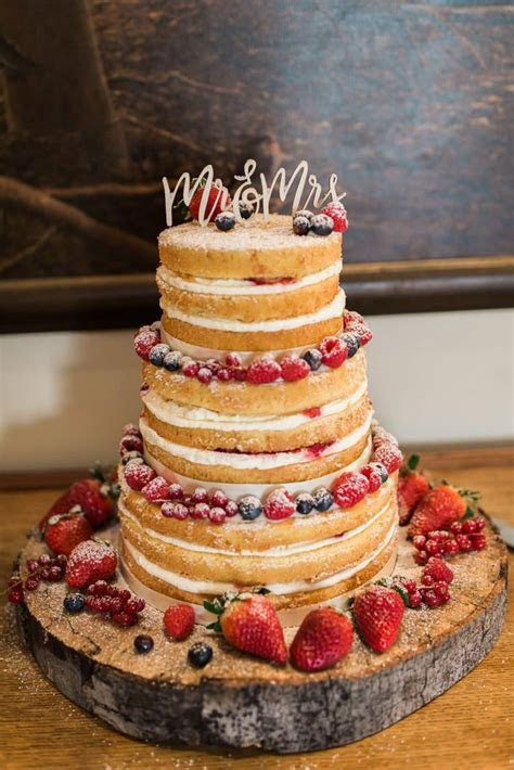 Yummy naked wedding cake with summer berries made by