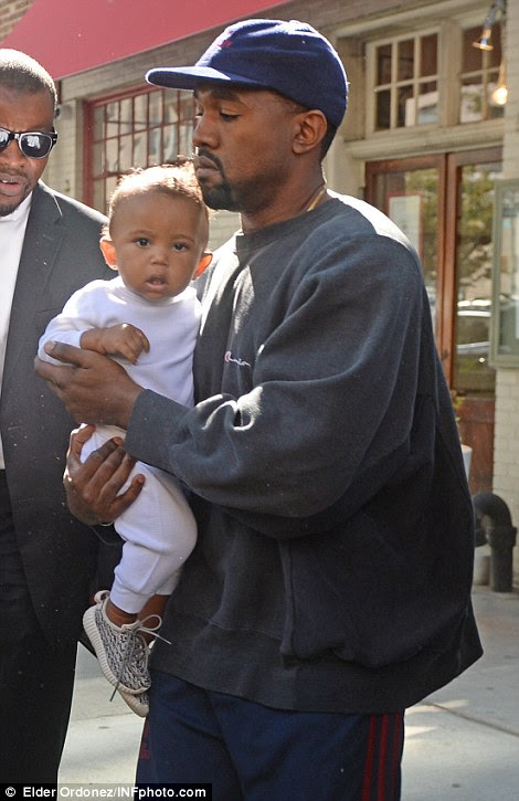 Daddy's boy: Young Saint looked bewildered by the media storm surrounding his parents on Thursday afternoon