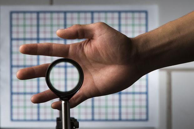 A imagem mostra o estudante Joseph Choi demonstrando o funcionamento das lentes que deixam qualquer coisa invisível (Foto: J. Adam Fenster/University of Rochester/Reuters)