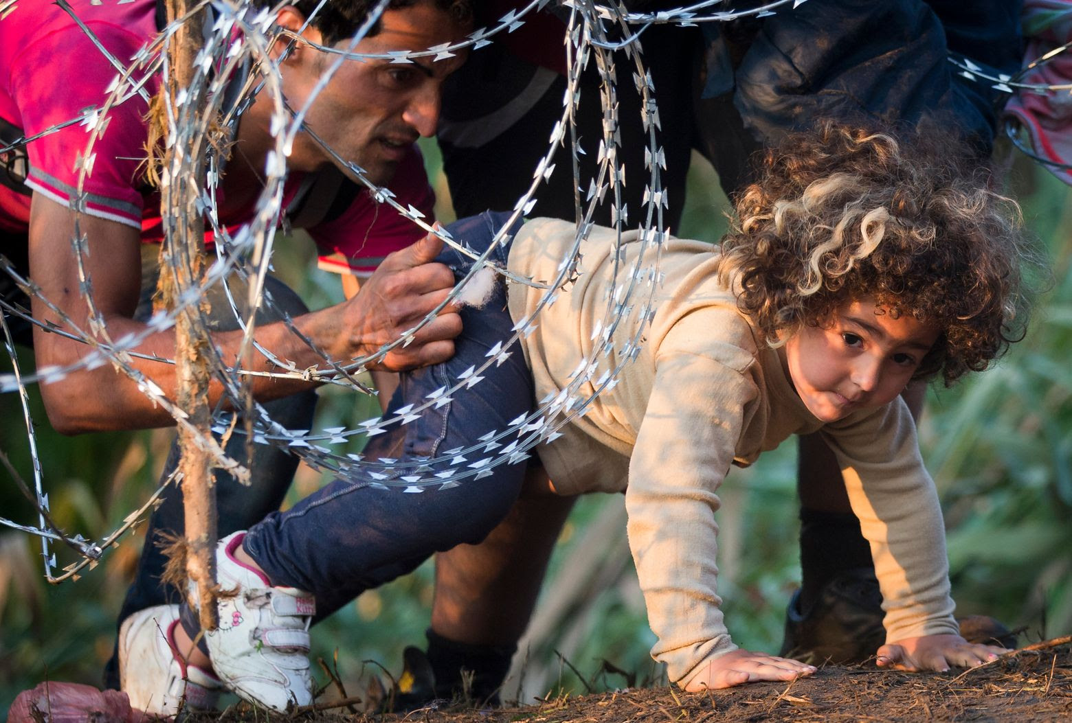 A refugee girl moves under barbed wire as she crosses from Serbia to Hungary, in Roszke, Thursday, Aug. (AP Photo/Darko Bandic)