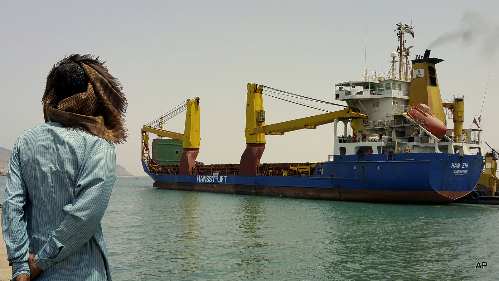 A Yemeni man looks at a World Food Program ship at the port of Aden, Yemen