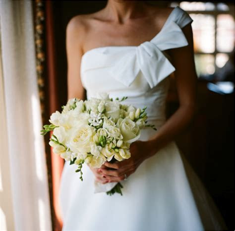 White one shoulder wedding dress and ivory bridal bouquet