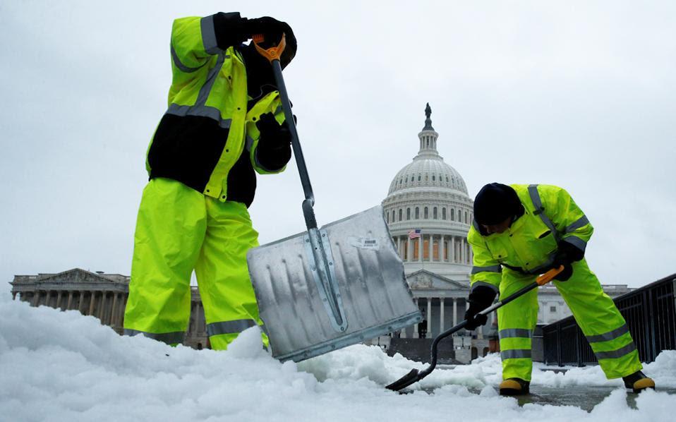 Υπάλληλοι του δήμου στην Ουάσιγκτον απομακρύνουν το χιόνι από τα πεζοδρόμια μπροστά στο Καπιτώλιο. Η σφοδρή χιονοθύελλα, που έπληττε από χθες την Ανατολική Ακτή των ΗΠΑ, ύστερα από έναν ασυνήθιστα ήπιο Φεβρουάριο, προκάλεσε έντονα προβλήματα στις μετακινήσεις, με περισσότερες από 2.500 ακυρώσεις πτήσεων από τα αεροδρόμια της περιοχής.