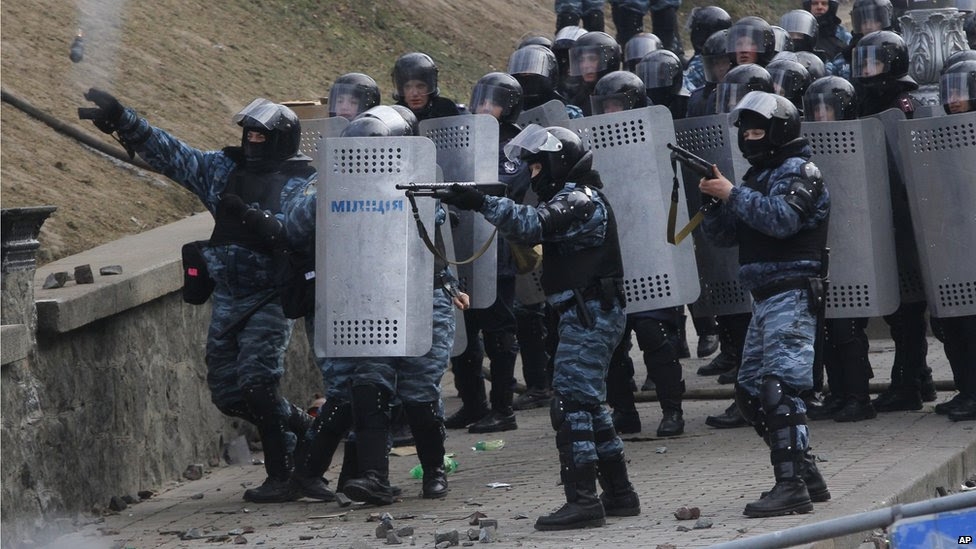 Riot police officers shoot rubber bullets and throw a stun grenade at anti-government protesters, during unrest in central Kiev, Ukraine, Monday 20 January 2014.