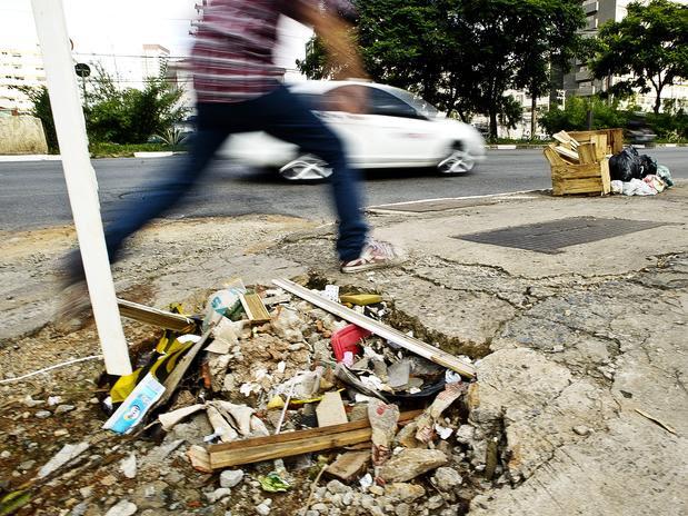Pedestre salta por cima de um grande buraco na calçada da avenida Engenheiro Luís Carlos Berrini, em São Paulo. Foto: Bruno Santos / Terra
