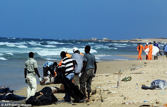 Rescue workers pull the bodies of illegal immigrants onto shore of al-Qarbole