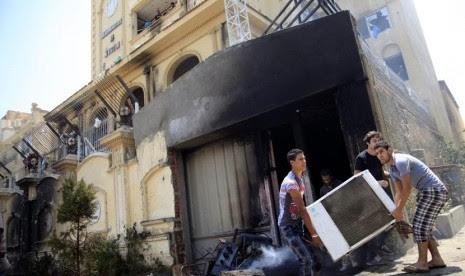 Para pengunjuk rasa menyerang dan menjarah markas Ikhwanul Muslimin di distrik Muqatam di Kairo, Senin (1/7).       (AP/Khalil Hamra)