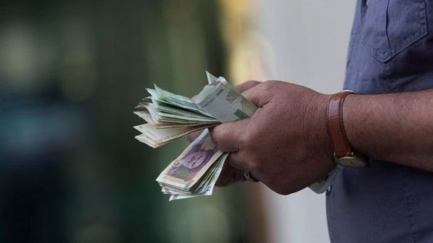 Photo of man holding Iranian currency