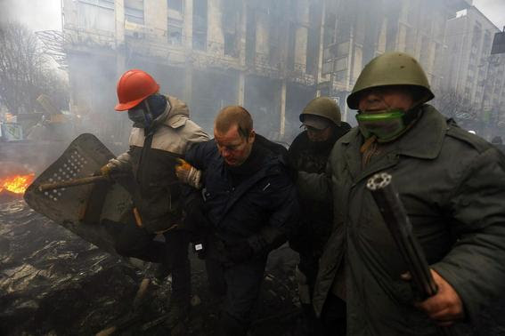 Anti-government protesters detain a policeman (2nd L) during clashes in the Independence Square in Kiev February 20, 2014. REUTERS-Yannis Behrakis