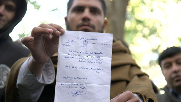 An interpreter holding a typical letter from the Taliban threatening to kill him