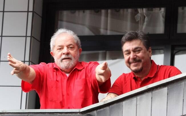 O ex-presidente Lula acena para simpatizantes da sacada de seu apartamento, no domingo