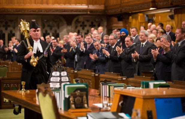 In this handout photo provided by the PMO, Prime Minister Stephen Harper (R) and all Members of Parliament applaud Kevin Vickers, Sergeant-at-Arms, during the reopening of Parliament on October 23, 2014 in Ottawa, Canada. The gunman, identified as Michael Zehaf-Bibeau, was shot and killed by Kevin Vickers while still inside the Parliament building.