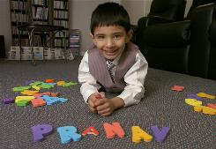 Six year-old Pranav Veera, who has a photographic memory and has tested in the very upper ranges of intelligence, poses with letters spelling his name, at home in Loveland, Ohio.