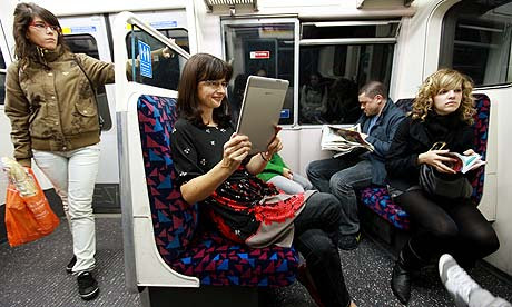 Woman reading a Kindle on the Tube