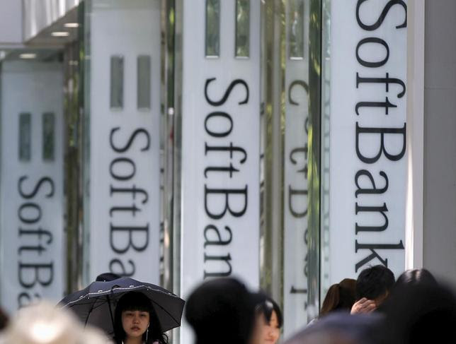 Pedestrians walk past logos of SoftBank Corp in front of its branch in Tokyo May 11, 2015. REUTERS/Toru Hanai