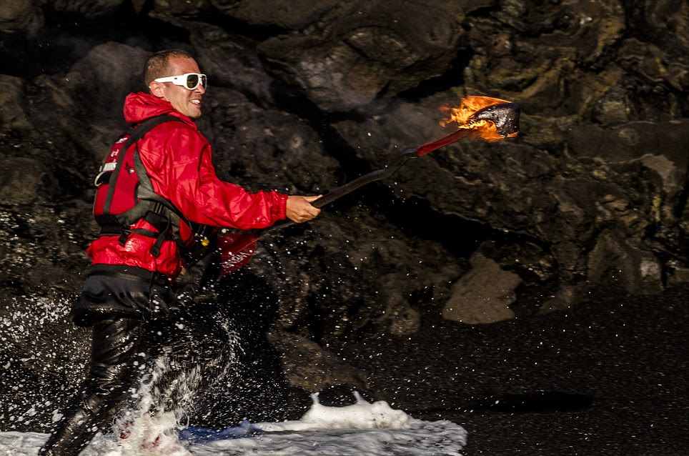 Fearless: Daredevil Pedro Oliva holds up his oar after molten lava set fire to it during a kayak expedition in Kauai, Hawaii
