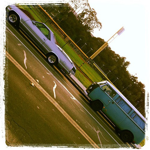 El Camino with a dingy in the back and a bus with a chow in it.