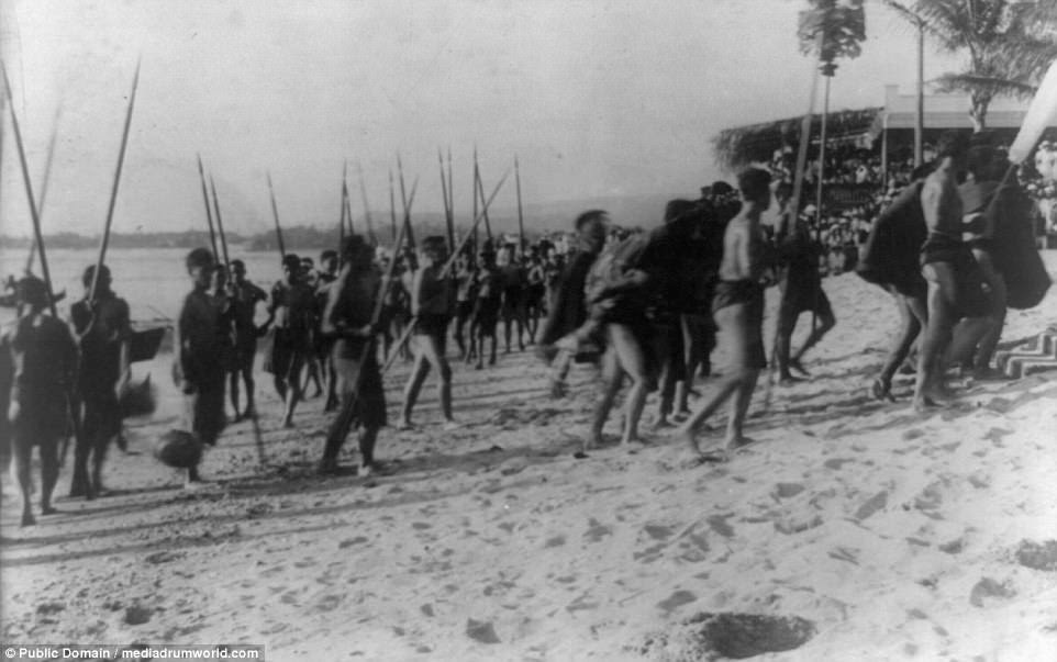 Hawaii natives return from competing in water sports during the 1913 Honolulu Festival. Many can be seen carrying spears