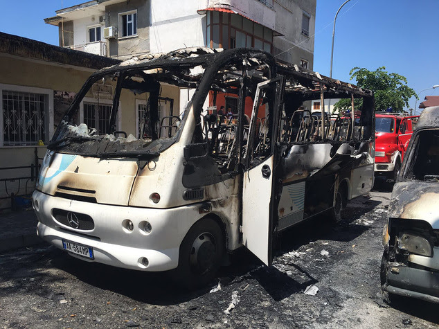 A burned bus is seen on the street in Kruja, 35 kilometers (22 miles) north of the capital, Tirana, Friday, May 27, 2016. Police say that one woman has died ...