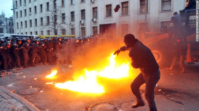 """A protester throws stones toward riot police on December 1. The crowd chanted """"Revolution!"""" and """"Down with the Gang"""" as it gathered in Kiev's iconic Independence Square and steered a bulldozer within striking distance of police barricades protecting the nearby presidential administration office."""