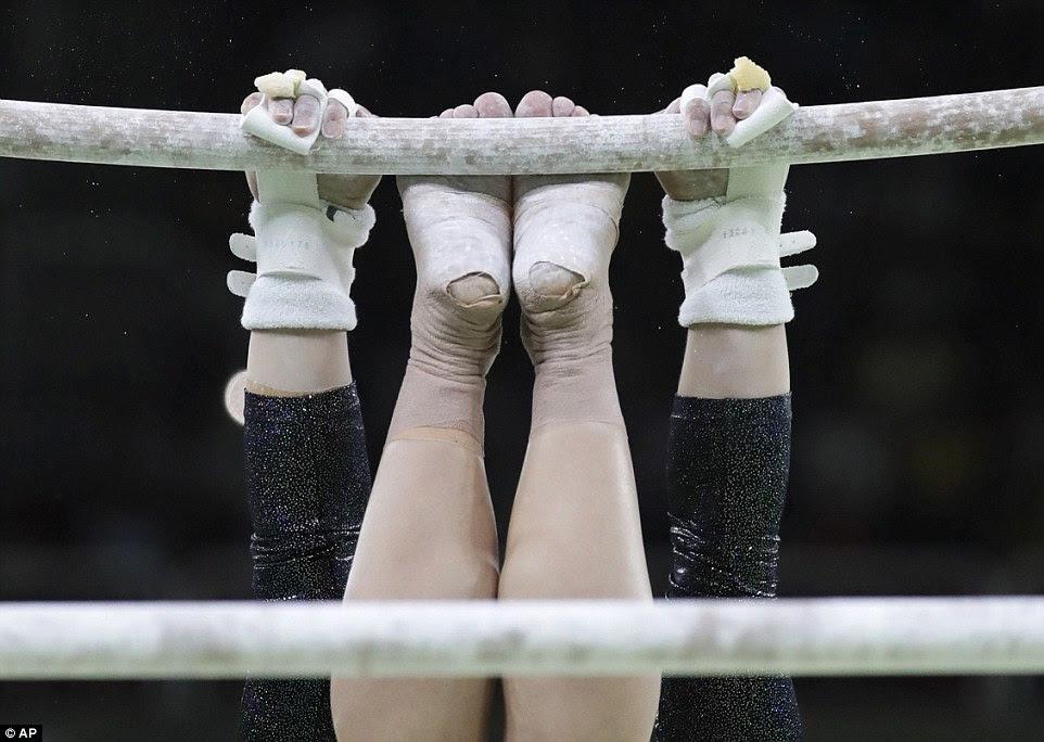 Erika Fasana da Itália prende o maior entre as barras assimétricas com as mãos e os pés, enquanto ela se qualifica para o all-around final,