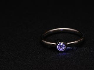 The ring on its own, on a black fabric background with a blue light shining through the diamond.