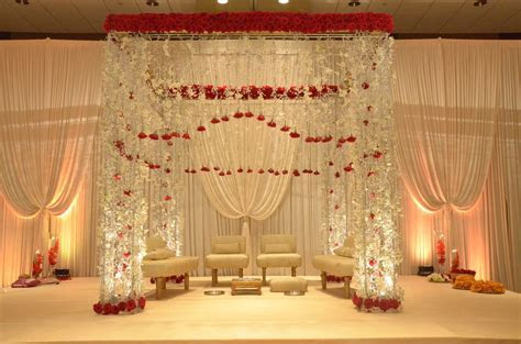 Crystal mandap design with hanging red roses. The perfect